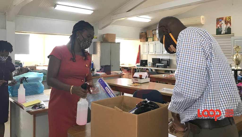 Princess Margaret Secondary School principal Jonathan Corbin (right) ticks off a teacher's name after distributing sanitiser and a face shield to her.
