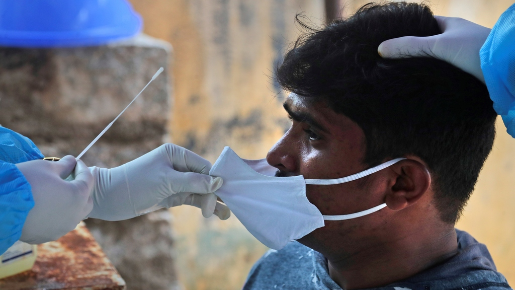 A health worker takes a nasal swab sample to test for COVID-19 in Hyderabad, India, Sunday, Sept. 13, 2020. India's coronavirus cases are now the second-highest in the world and only behind the United States. (AP Photo/Mahesh Kumar A.)