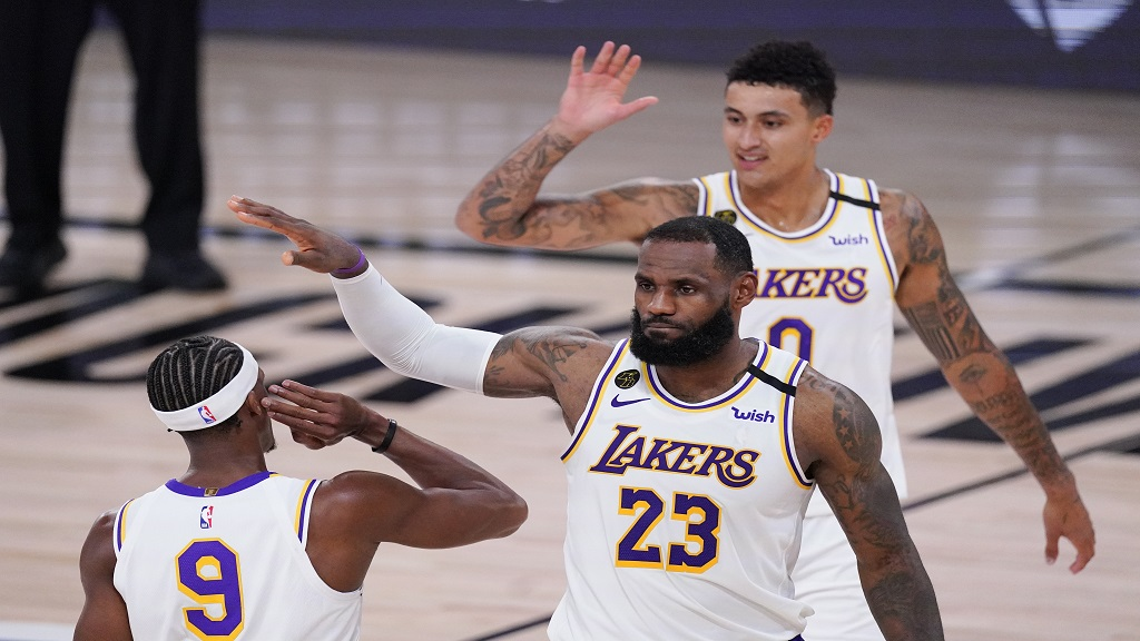 Los Angeles Lakers' LeBron James, Kyle Kuzma, rear, and Rajon Rondo (9) celebrate during the second half of an NBA conference semifinal playoff basketball game against the Houston Rockets Tuesday, Sept. 8, 2020, in Lake Buena Vista, Fla. (AP Photo/Mark J. Terrill).