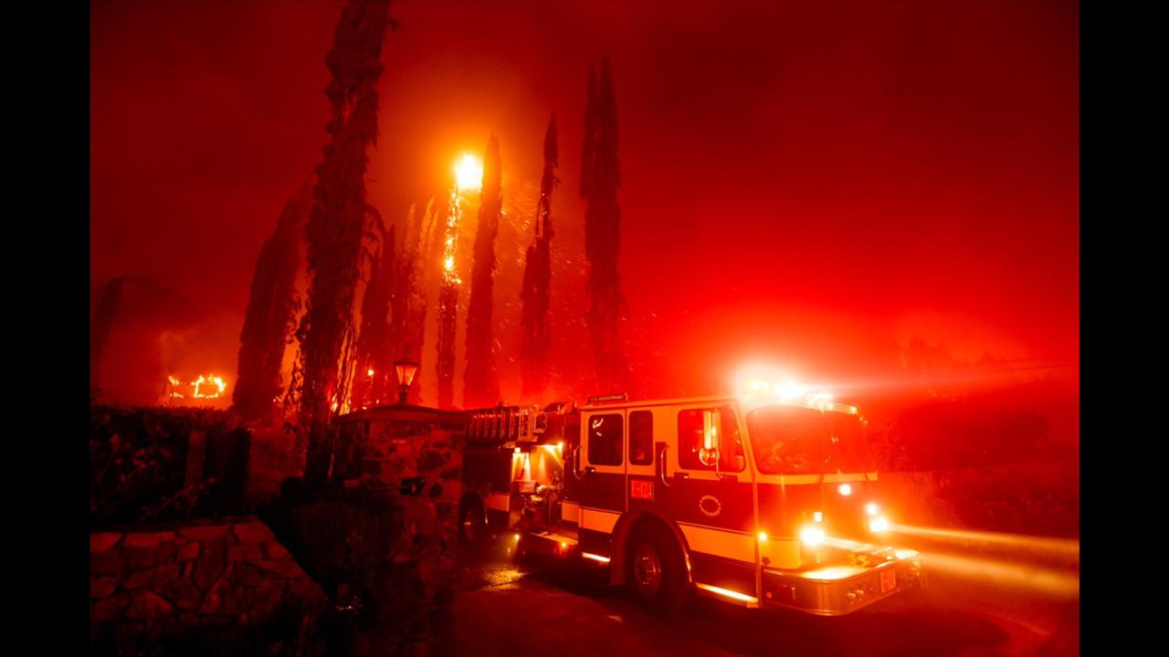 A fire engine leaves a burning property as the Glass Fire tears through St. Helena, California on Sunday, September 27, 2020. (AP Photo/Noah Berger)