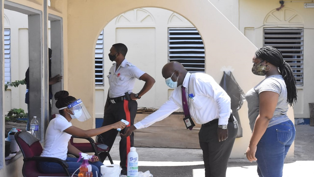 A special services voter has his temperature checked at the Greater Portmore Police Station on Monday. (Photo: Marlon Reid)