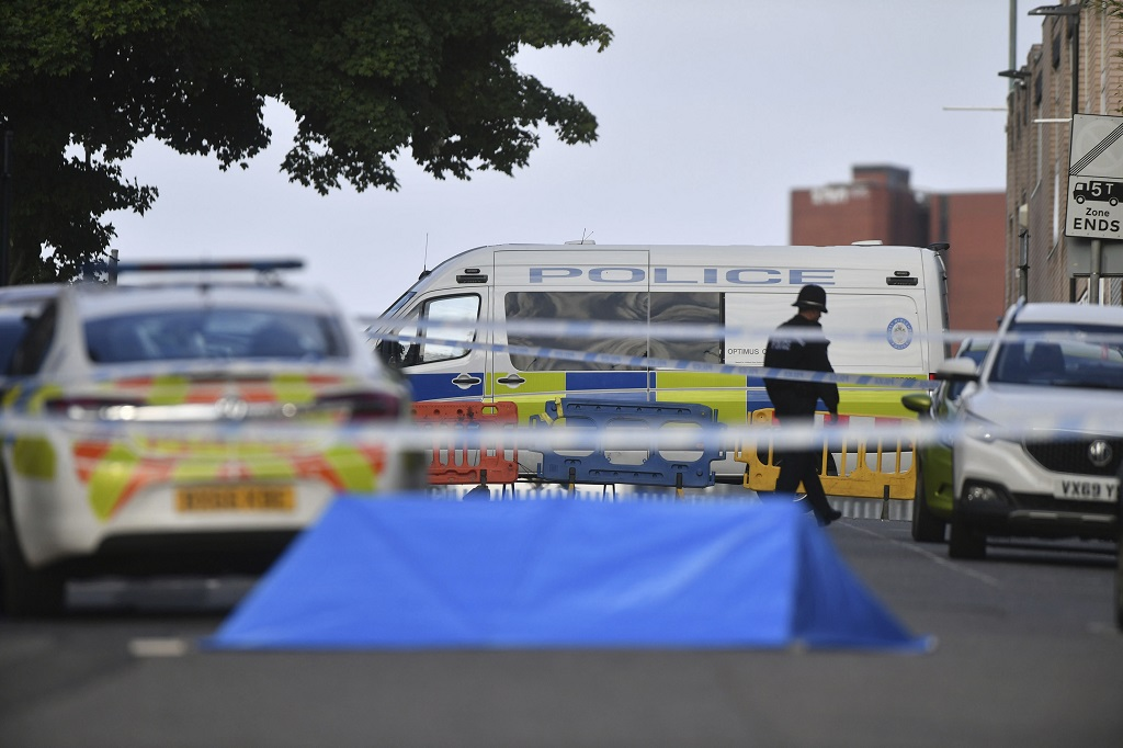 A police officer and vehicles are seen at a cordon in Irving Street in Birmingham after a number of people were stabbed in the city centre, Sunday, September 6, 2020. (Jacob King/PA via AP)