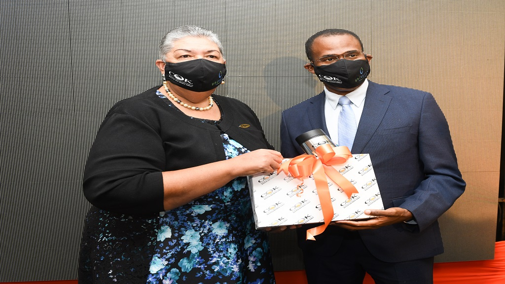 Ambassador Aloun Ndombet-Assamba (left) CEO of COK Sodality Credit Union presents a token of appreciation  Dr. Nigel Clarke, Minister of Finance & the Public Service  following his address at the launch of COK's New Core Banking System.