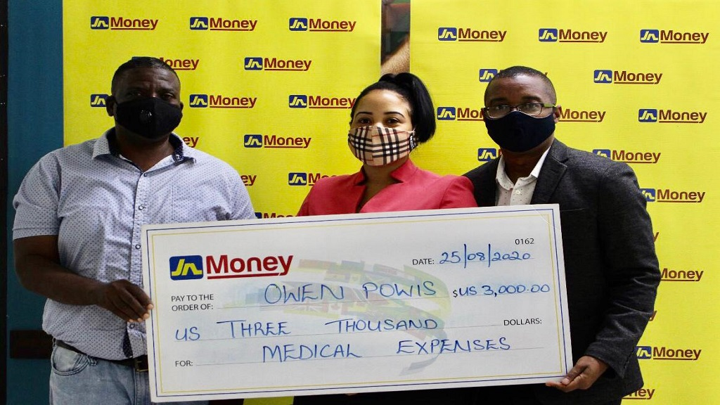 Owen Powis, (left) accepts a donation from Horace Hines (right) general manager, JN Money Services, and Melissa Draggon, operations supervisor, at JN Money services, owners and operators of the JN Money brand to assist with his medical treatment.