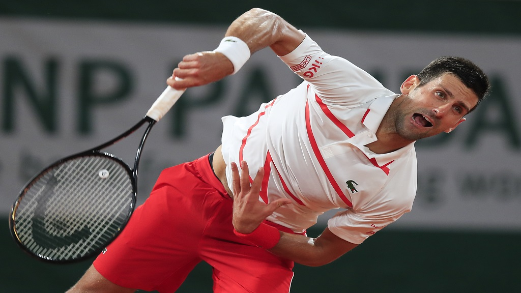 Serbia's Novak Djokovic serves against Sweden's Mikael Ymer in the first round match of the French Open tennis tournament at the Roland Garros stadium in Paris, France, Tuesday, Sept. 29, 2020. (AP Photo/Michel Euler).