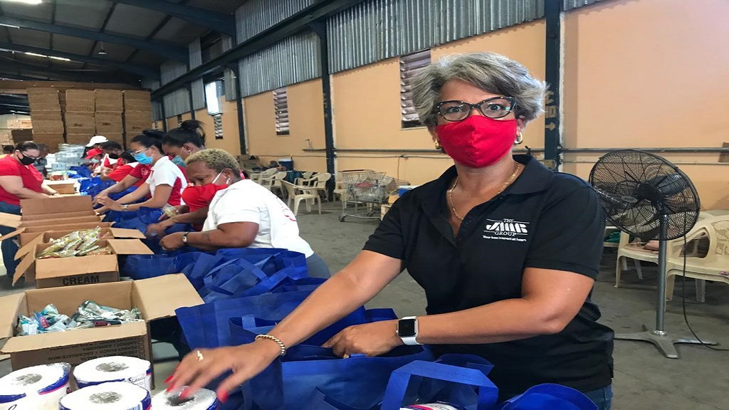 Kim Mair (right), vice chair of the Council of Voluntary Social Services and  chief executive officer of JMMB Joan Duncan Foundation packing food packages with other volunteers for distribution under the PSOJ COVID-19 Jamaica Response Fund.