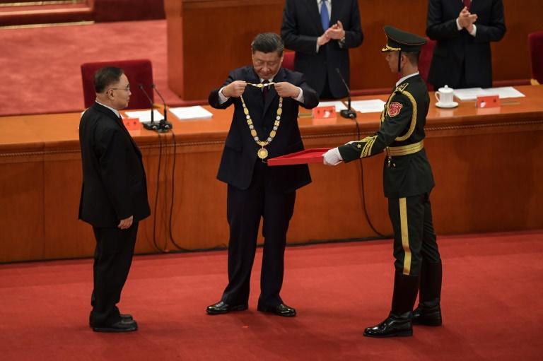 Le président chinois Xi Jinping (centre) remet une médaille à un expert en médecine traditionnelle lors d'une cérémonie à Pékin le 8 septembre 2020.