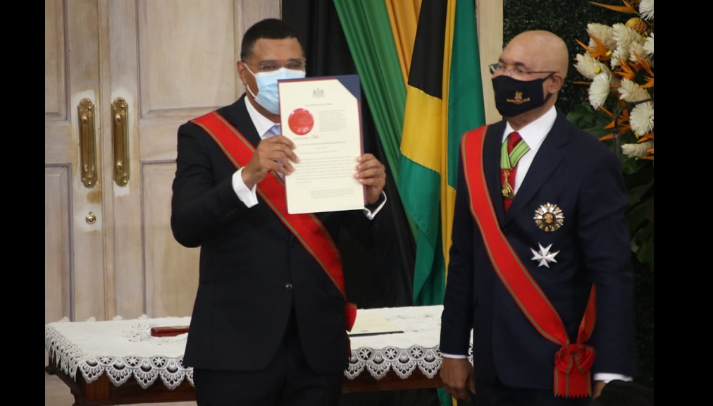 Prime Minister Andrew Holness displays the Instrument of Appointment to the Office of Prime Minister after being sworn in on Monday. Governor General Sir Patrick Allen looks on.