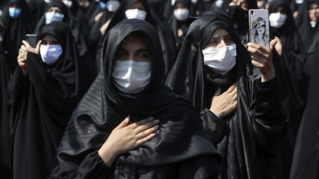 FILE - In this Sunday, Aug. 30, 2020 file photo, people wearing protective face masks to help prevent spread of the coronavirus mourn during an annual ceremony commemorating Ashoura in Tehran, Iran. The confirmed death toll from the coronavirus has gone over 50,000 in the Middle East as the pandemic continues. That's according to a count Thursday, Sept. 3, 2020, from The Associated Press, based on official numbers offered by health authorities across the region. (AP Photo/Ebrahim Noroozi, File)
