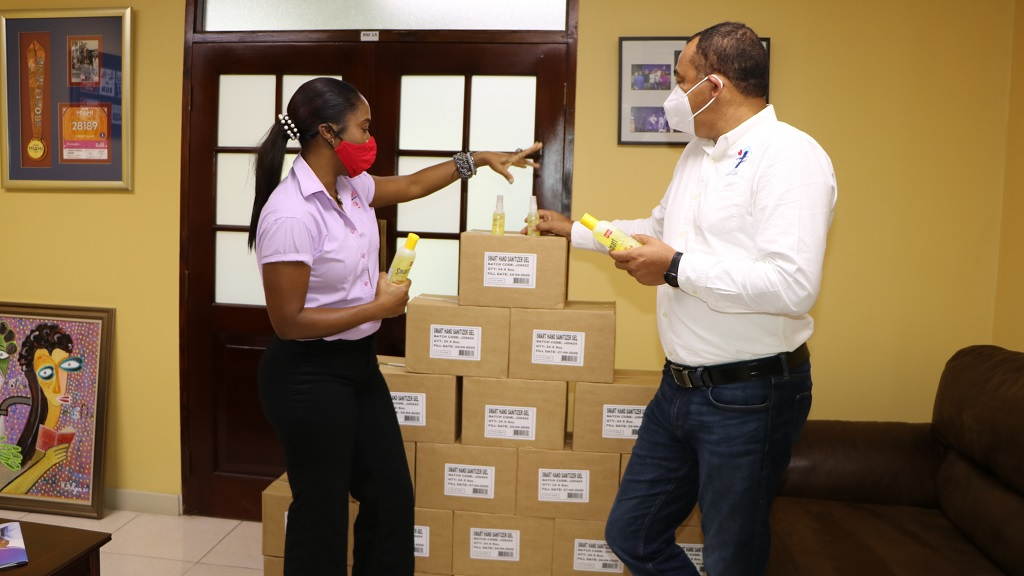 Minister of Health and Wellness, Dr Chris Tufton (right), checks out some of the hand sanitisers being donated for health sector workers by Orion Manufacturing Services (OMS). With him is Tanya Hird, Operations and Business Development Manager at OMS.