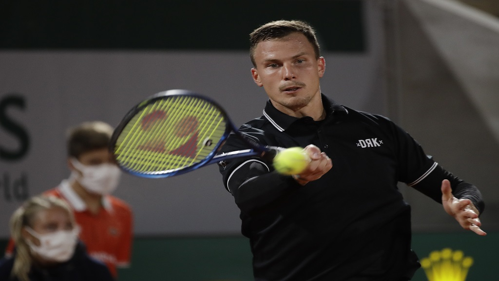 Hungary's Marton Fucsovics plays a shot against Russia's Daniil Medvedev in the first round match of the French Open tennis tournament at the Roland Garros stadium in Paris, France, Monday, Sept. 28, 2020. (AP Photo/Alessandra Tarantino).