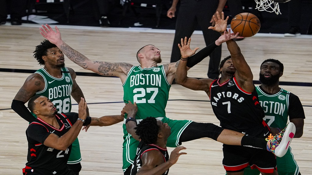 Boston Celtics center Daniel Theis (27) tries to shoot over Toronto Raptors guard Kyle Lowry (7) during the second half of an NBA conference semifinal playoff basketball game Wednesday, Sept. 9, 2020, in Lake Buena Vista, Fla. (AP Photo/Mark J. Terrill).