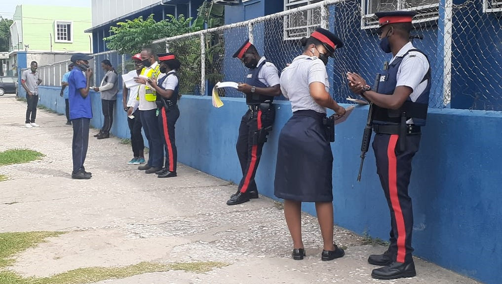 Denham Town police officers busy writing tickets for rule breakers on Wednesday.