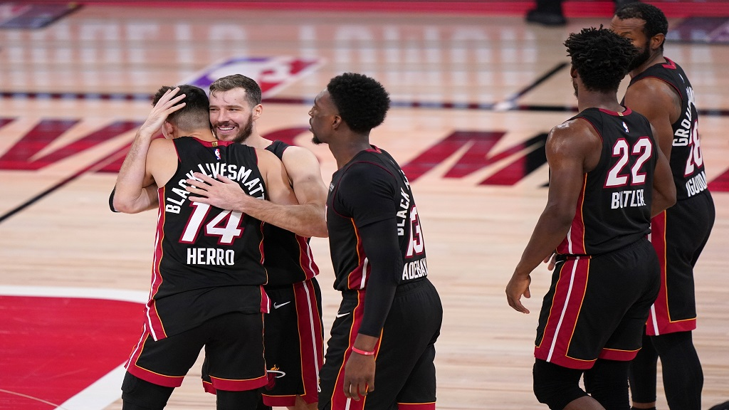 Miami Heat's Tyler Herro (14), Goran Dragic, second from left, Bam Adebayo, centre, Jimmy Butler (22) and Andre Iguodalal, right rear, celebrate as they walk off the court celebrating. (AP Photo/Mark J. Terrill).
