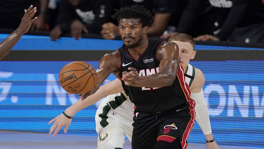 Miami Heat's Jimmy Butler passes in front of Milwaukee Bucks' Donte DiVincenzo, rear, in the second half of an NBA conference semifinal playoff basketball game Friday, Sept. 4, 2020, in Lake Buena Vista, Fla. (AP Photo/Mark J. Terrill).