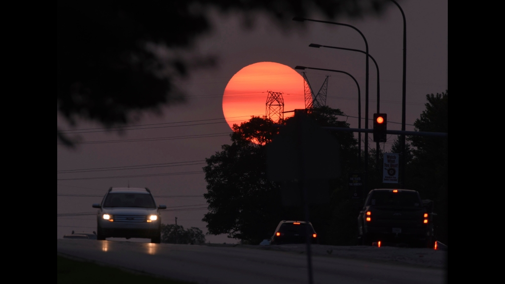 Traffic flows on Townline Road as a hazy sun sets in Vernon Hills, Illinois