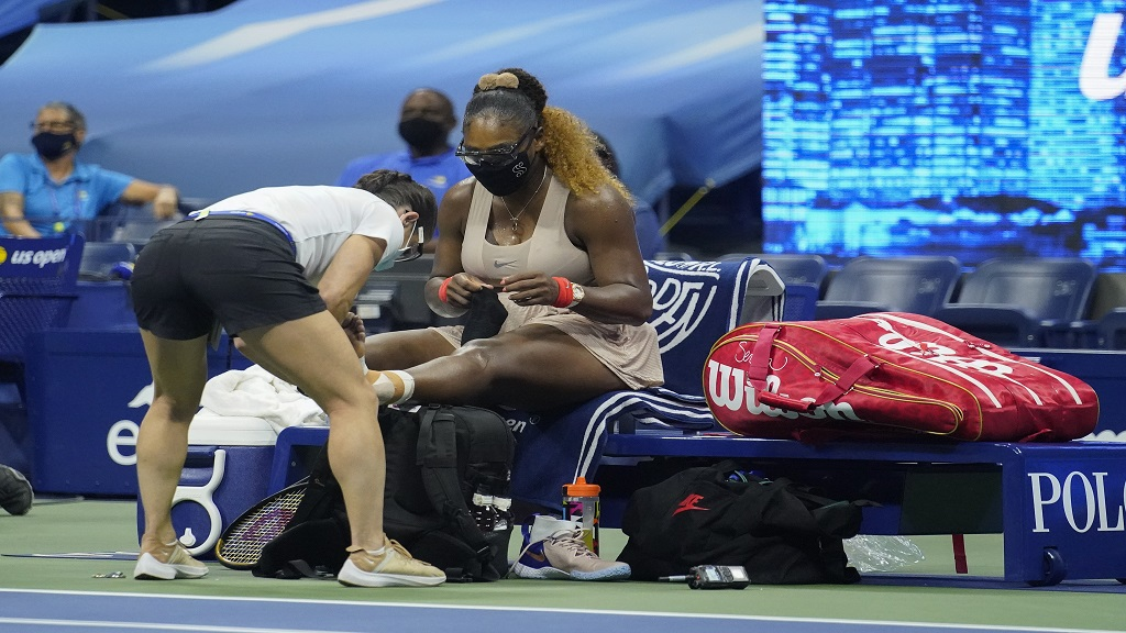 Serena Williams, of the United States, has her ankle taped by a trainer during a medical timeout during a semifinal match of the US Open tennis championships against Victoria Azarenka, of Belarus, Thursday, Sept. 10, 2020, in New York. (AP Photo/Frank Franklin II).