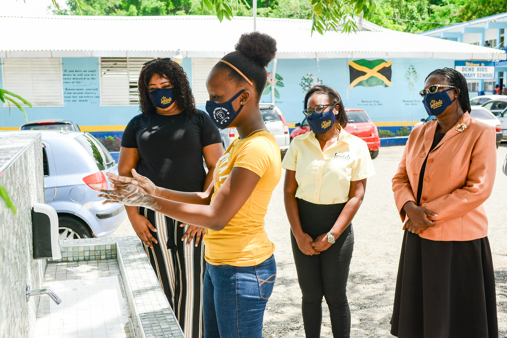 Jody-Ann Clarke, student at Ocho Rios Primary School washes her hands at the newly constructed hand wash station with her mother, Akayla Riley, Sandals Foundation Public Relations Manager, Patrice Gilpin and Principal at the Ocho Rios Primary School, Suzette Barnes-Wilson looking on.