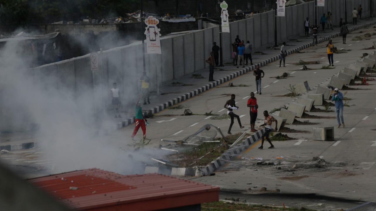 Protesters run away as police officers use teargas to disperse people demonstrating against police brutality in Lagos, Nigeria, Wednesday October 21, 2020. After 13 days of protests against alleged police brutality, authorities have imposed a 24-hour curfew in Lagos, Nigeria's largest city, as moves are made to stop growing violence. ( AP Photo/Sunday Alamba)
