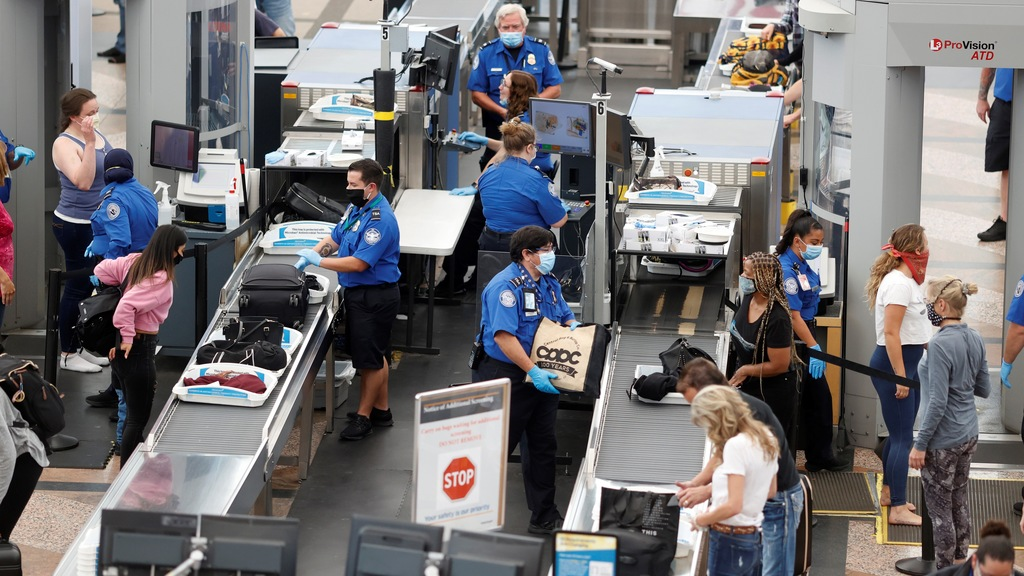 FILE - In this June 10, 2020 file photo, Transportation Security Administration agents process passengers at the south security checkpoint at Denver International Airport in Denver, as travelers deal with the effects of the new coronavirus. (AP Photo/David Zalubowski, File)