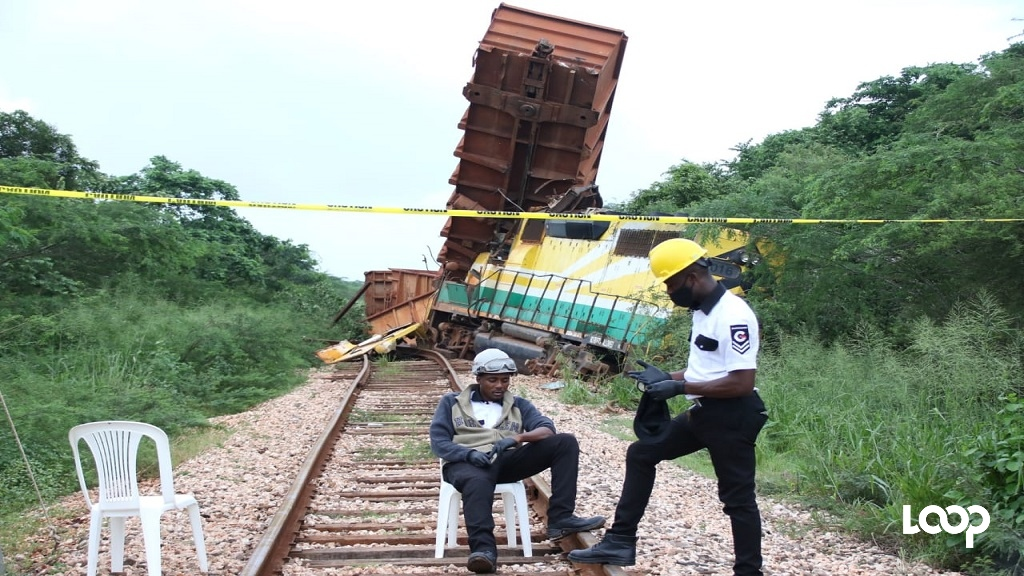 Security officers contracted to Jamalco at the site where one of the company's bauxite trains derailed during recent heavy rains.