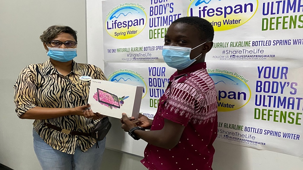 Leandro Bell, Grade 9  at Titchfield High School is excited to receive a tablet from Nayana Williams CEO Lifespan Spring Water Company.