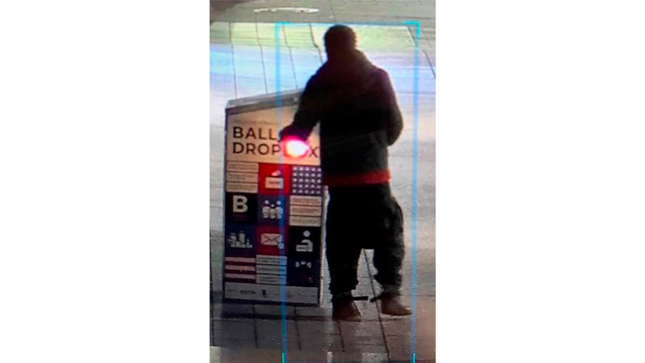This surveillance image provided by the Boston Police Department shows a man approaching a ballot drop box outside the Boston Public Library, early Sunday, October 25, 2020, in downtown Boston. (Courtesy of Boston Police Department via AP)