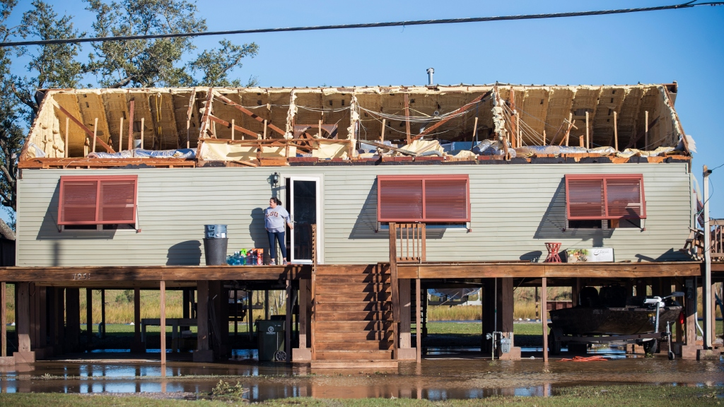 A woman walks out of a house where the roof was torn away during Hurricane Zeta, as people begin the process of cleaning and rebuilding in Chauvin, Louisiana, Thursday, October 29, 2020. Photo: Chris Granger/The Times-Picayune/The New Orleans Advocate/ AP