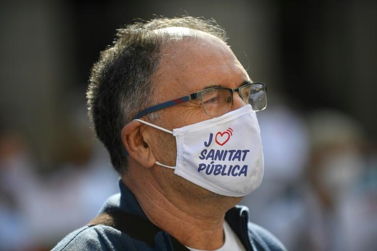 """Un soignant porte un masque """"J'aime la santé publique"""" pendant une manifestation réclamant de meilleures conditions de travail devant la Generalitat à Barcelone le 29 octobre 2020"""