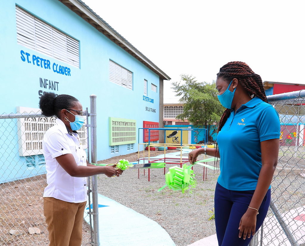 Karen Reynolds (left), Principal of St. Peter Claver Primary & Infant School and Michelle-Ann Letman, Manager, Public Relations and Corporate Social Responsibility, Sagicor Group Jamaica, cut a ribbon to officially handover the newly renovated play area at the school's Infant Department.