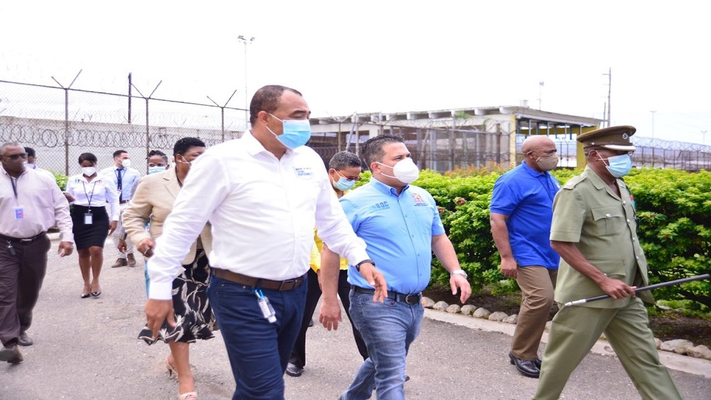 Minister without Portfolio in the Ministry of National Security, Senator Matthew Samuda (third right, foreground), and Minister of Health and Wellness, Dr Christopher Tufton (centre, foreground), visiting the Horizon Adult Remand Centre in the Corporate Area to observe the implementation of COVID-19 protocols established by the Health Ministry to help prevent the spread of the virus.
