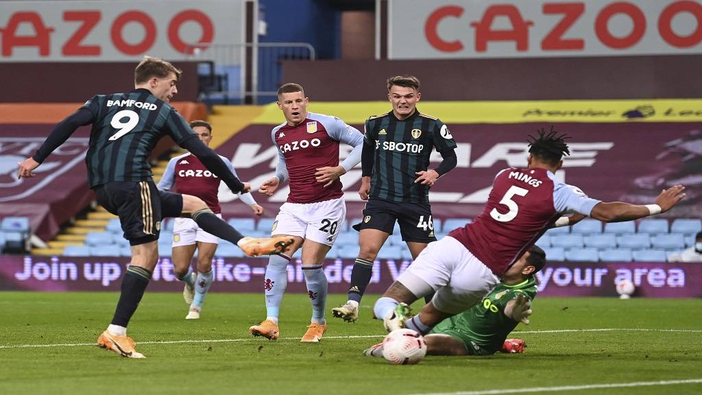 Leeds United's Patrick Bamford, left, shoots to score during the English Premier League football match against Aston Villa at Villa Park in Birmingham, England, Friday, Oct. 23, 2020. (Laurence Griffiths/Pool via AP).