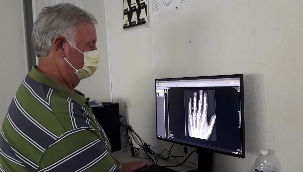 Advisory Board Member, Issa Trust Foundation, Rob Barkema, looks at an X-ray image produced by the new digital system at the Falmouth General Hospital in Trelawny.