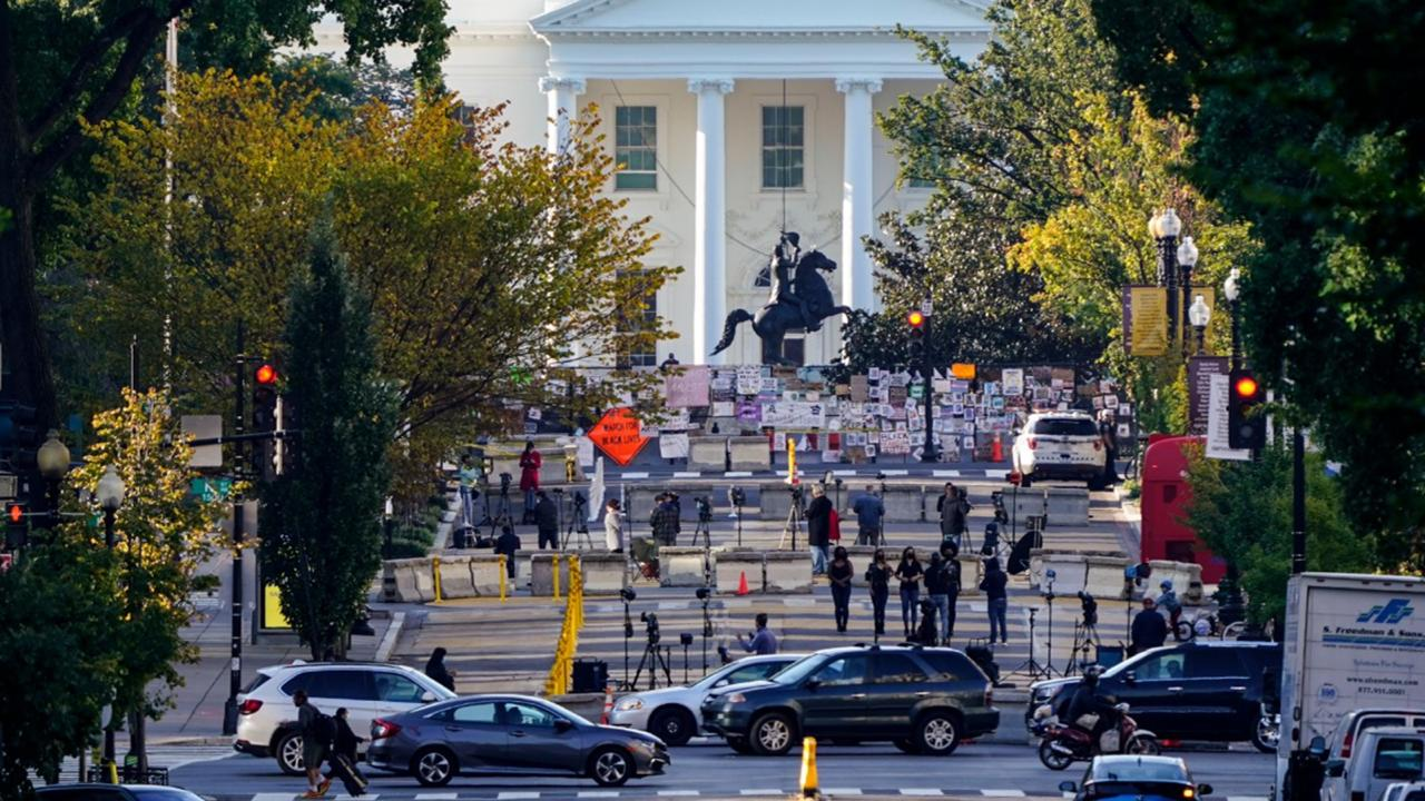 The White House is seen in Washington, early Tuesday, October 6, 2020, the morning after President Donald Trump returned from the hospital where he was treated for COVID-19. Traffic moves along K Street NW as TV crews set up in Black Lives Matter Plaza. (AP Photo/J. Scott Applewhite)