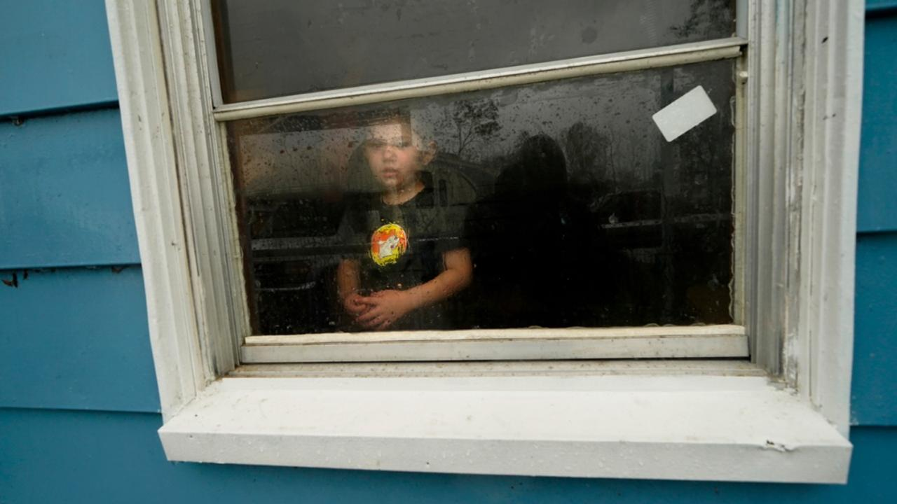 Hunter Fontenot, 3, looks out the window of his uncle's house, to which his family temporarily relocated to ride out Hurricane Delta which is expected to make landfall later in the day, in Lake Charles, La., Friday, October 9, 2020. (AP Photo/Gerald Herbert)