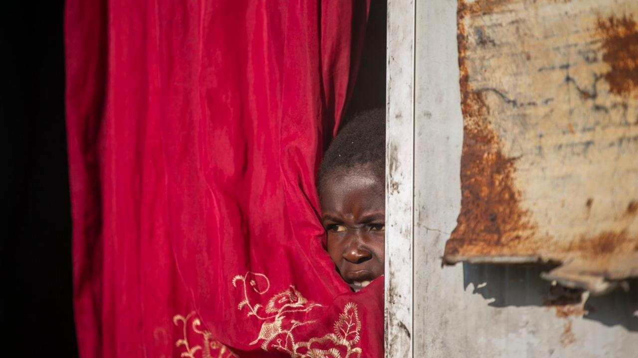 Jonelson Princeton, 7, who survived cholera as a newborn, peers out from inside his home which was once used as an office, on a former UN base where he lives with his parents and grandmother in Mirebalais, Haiti, Monday, October 19, 2020. (AP Photo/Dieu Nalio Chery)