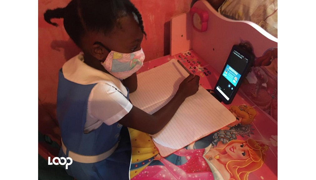 Tianna Thompson of Alpha Primary School participates in a class exercise via a smartphone device on Monday at the start of the new academic year.