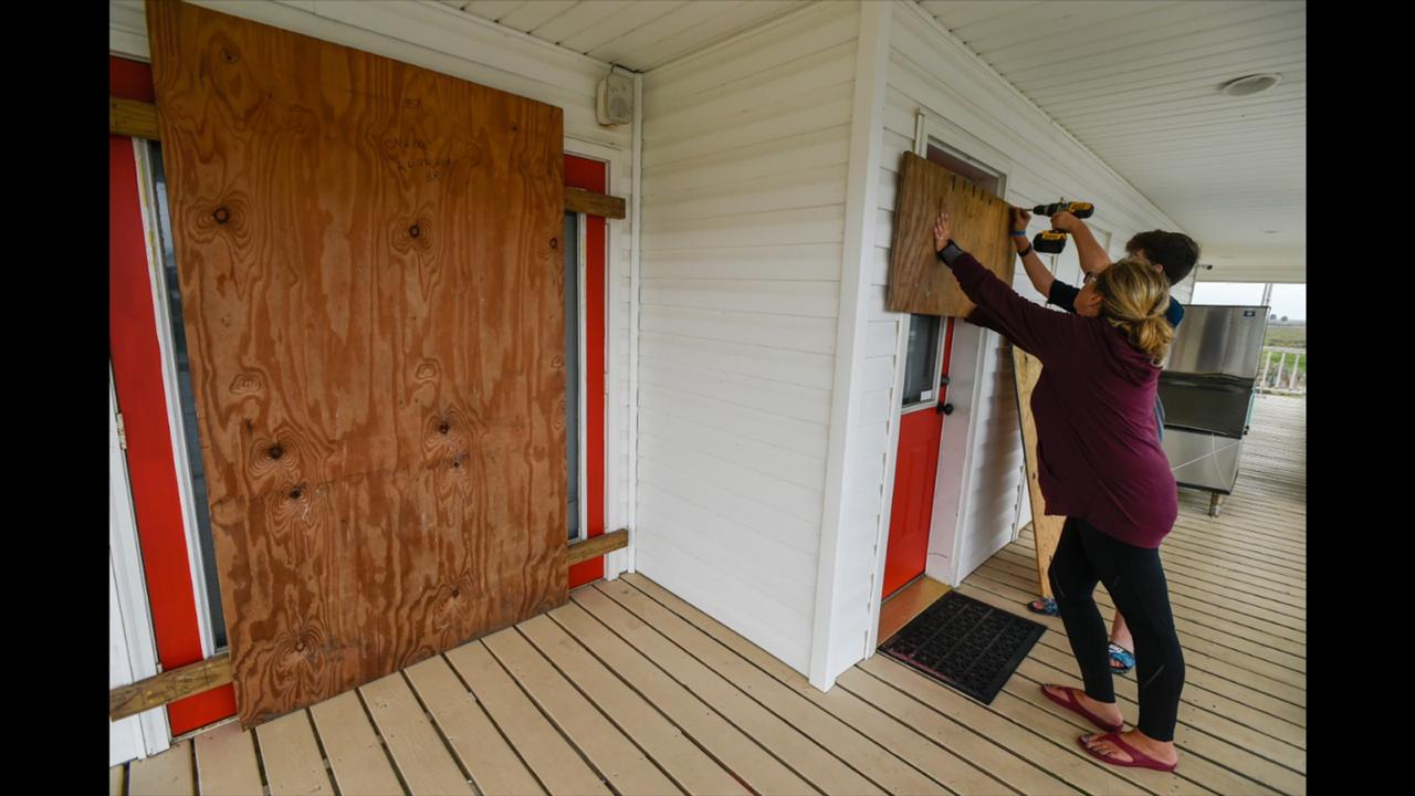 Residents Mamie Russo and her son Cole attach wood to their front door while preparing for Hurricane Delta on Thursday, October 8, 2020, in Cypremort Point, La. (Brad Kemp/The Advocate via AP)