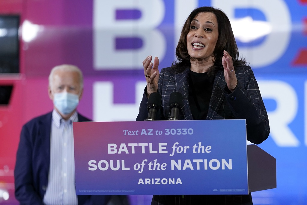 In this October 8, 2020, photo, Democratic vice presidential candidate Senator Kamala Harris, D-Calif., speaks at Carpenters Local Union 1912 in Phoenix, as Democratic presidential candidate former vice president Joe Biden listens. Biden's presidential campaign says Harris will suspend in-person events until October 19, after two people associated with the campaign tested positive for coronavirus. (AP Photo/Carolyn Kaster)