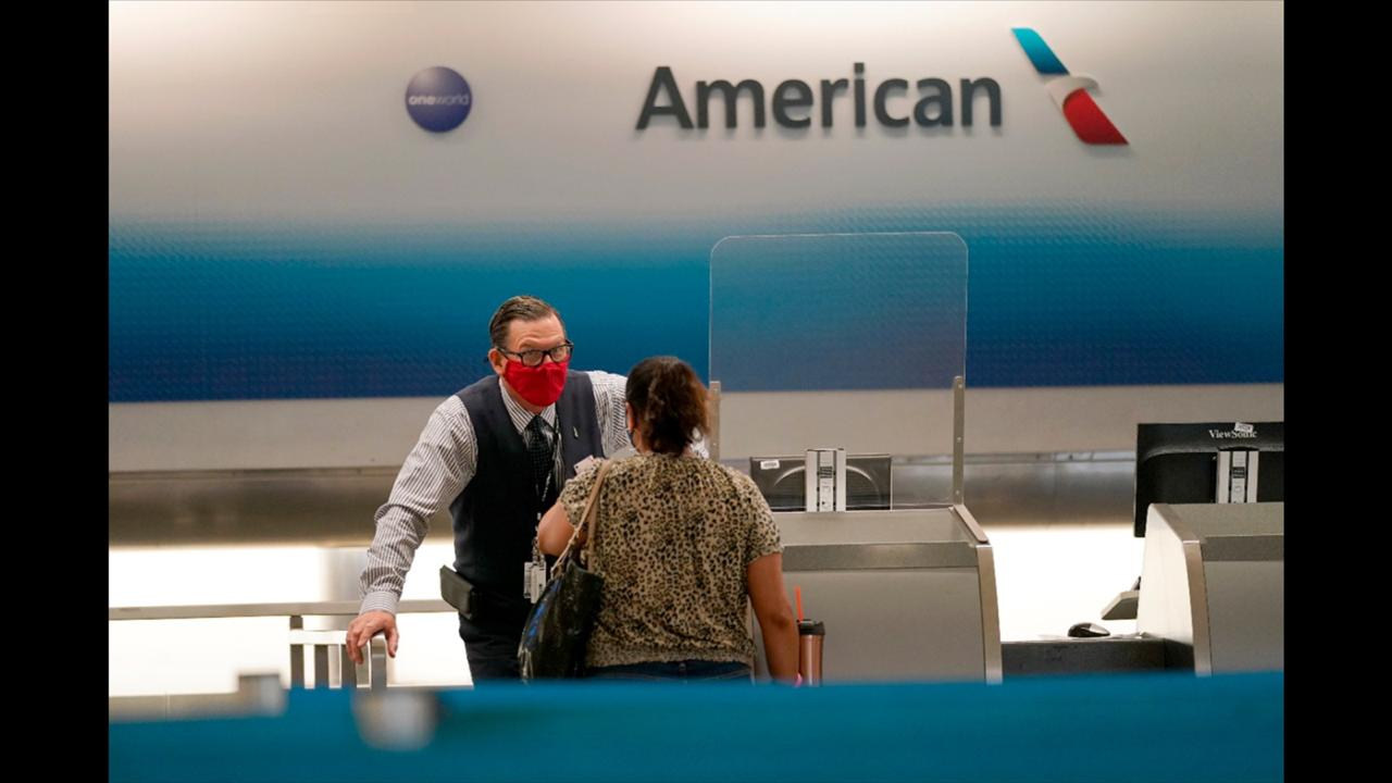 American Airlines ticket agent Henry Gemdron, left, works with a customer at Miami International Airport during the coronavirus pandemic, Wednesday, September 30, 2020, in Miami. The airline industry has been decimated by the pandemic. The Payroll Support Program given to the airlines as part of the CARES Act runs out Thursday. (AP Photo/Lynne Sladky)