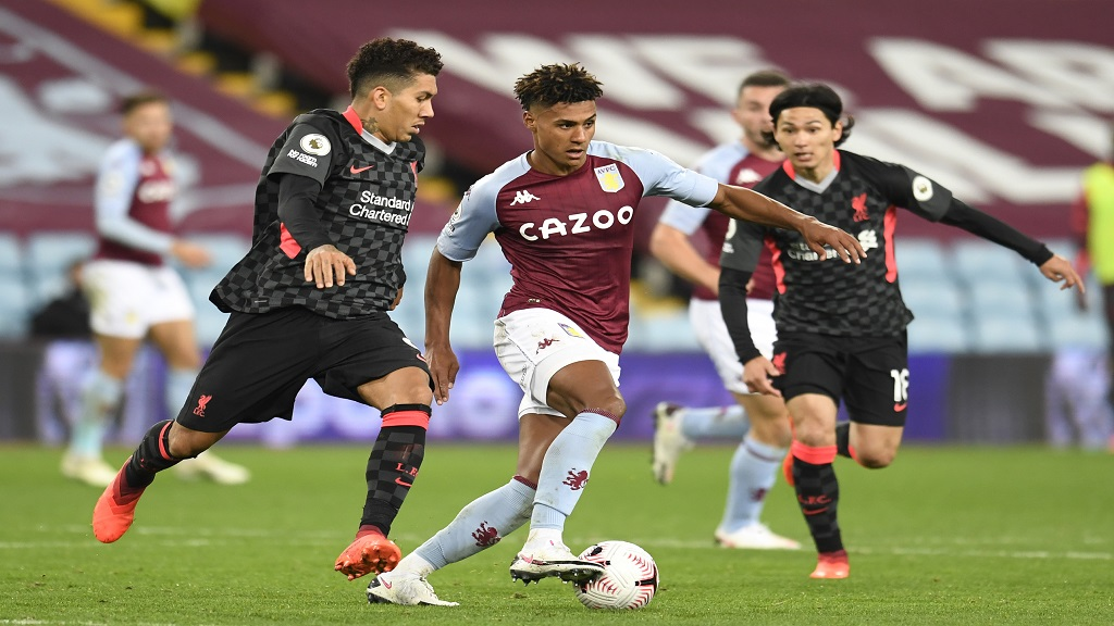 Aston Villa's Ollie Watkins, centre, is challenged by Liverpool's Roberto Firmino, left, and Takumi Minamino during the English Premier League football match at the Villa Park stadium in Birmingham, England, Sunday, Oct. 4, 2020. (Peter Powell/Pool via AP).