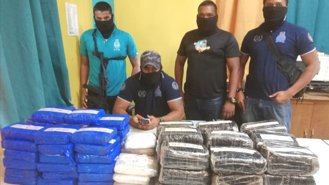Police officers stand over a million-dollar marijuana find in the Sangre Grande district.