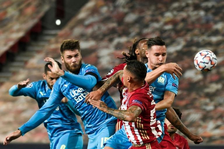 Le défenseur croate de Marseille Duje Caleta-Car (g) et l'attaquant Florian Thauvin (d) au duel avec un joueur de l'Olympiakos lors du match de groupes de la Ligue des champions, au Pirée, le 21 octobre 2020 afp.com - LOUISA GOULIAMAKI