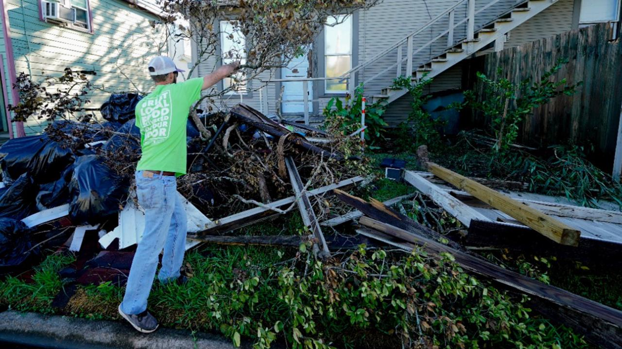 Caleb Cormier moves debris after Hurricane Delta moved through, Saturday, October 10, 2020, in Lake Charles, La. Delta hit as a Category 2 hurricane with top winds of 100 mph (155 kph) before rapidly weakening over land. (AP Photo/Gerald Herbert)