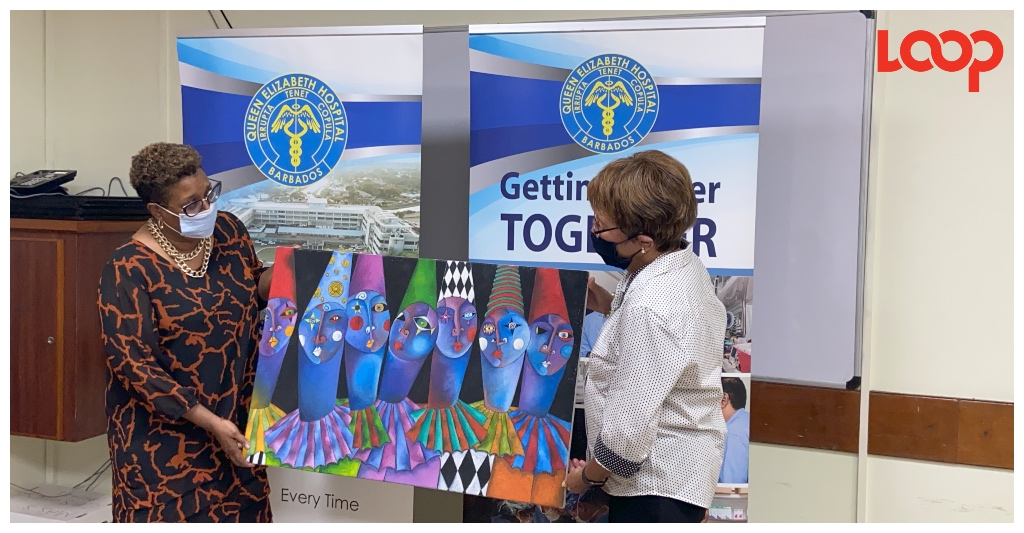 (From Left) Executive chairman of the Queen Elizabeth Hospital, Juliette Bynoe-Sutherland receives a Sandra Evans-Gibbs art piece from director of the Caribbean Art Gallery, Hazel-Ann May-Batson.