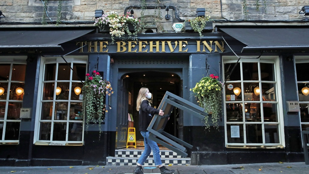 A worker removes tables from outside the Beehive Inn, as temporary restrictions announced by First Minister Nicola Sturgeon to help curb the spread of coronavirus have come into effect from 6pm, in Edinburgh, Friday, Oct. 9, 2020. (Andrew Milligan/PA via AP