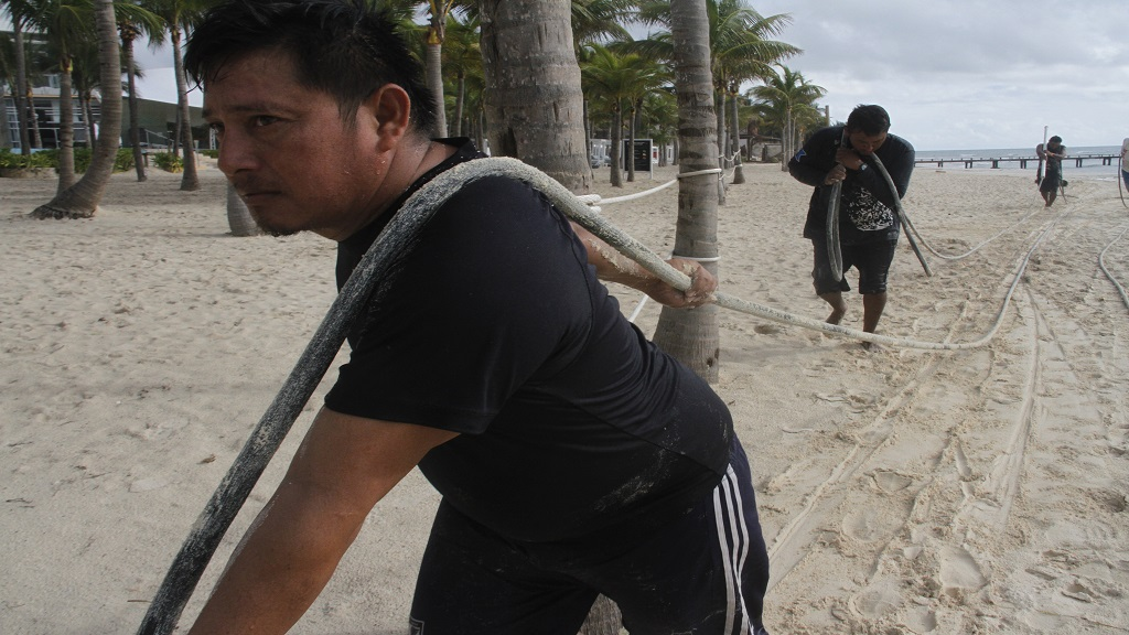 Workers retreive equipment before Hurricane Delta arrives near Playa del Carmen, Mexico, early Tuesday, October 6, 2020. (AP Photo/Tomas Stargardter)