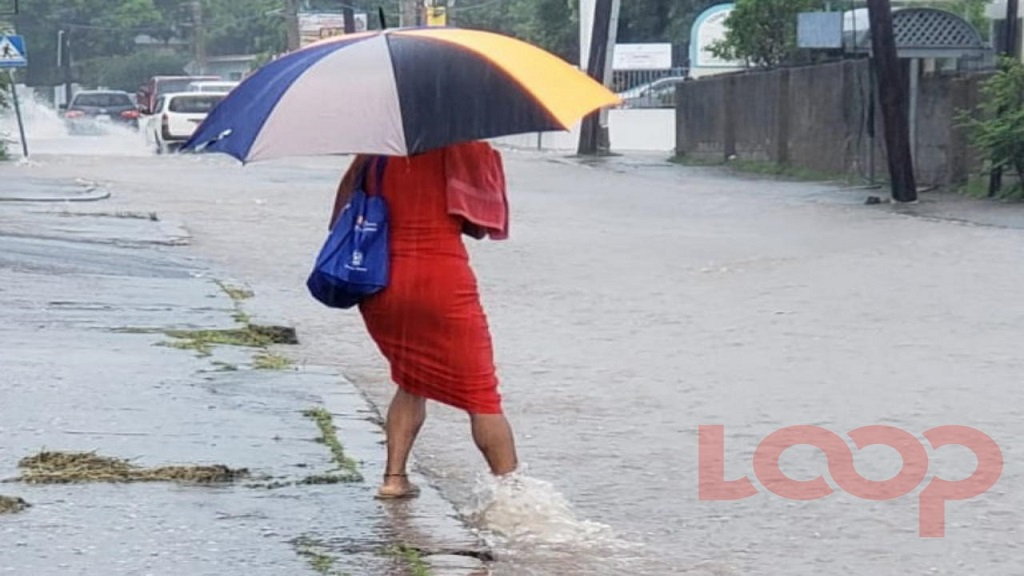 A woman attempts to cross a flooded street during heavy rainfall in the Corporate Area on Wednesday.