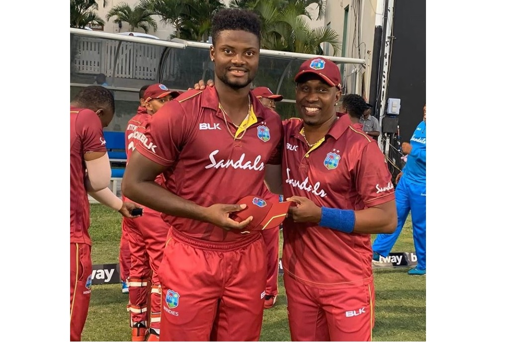 Romario Shepherd (left) receives his T20I debut cap from Dwayne Bravo in Antigua on October 21, 2020.