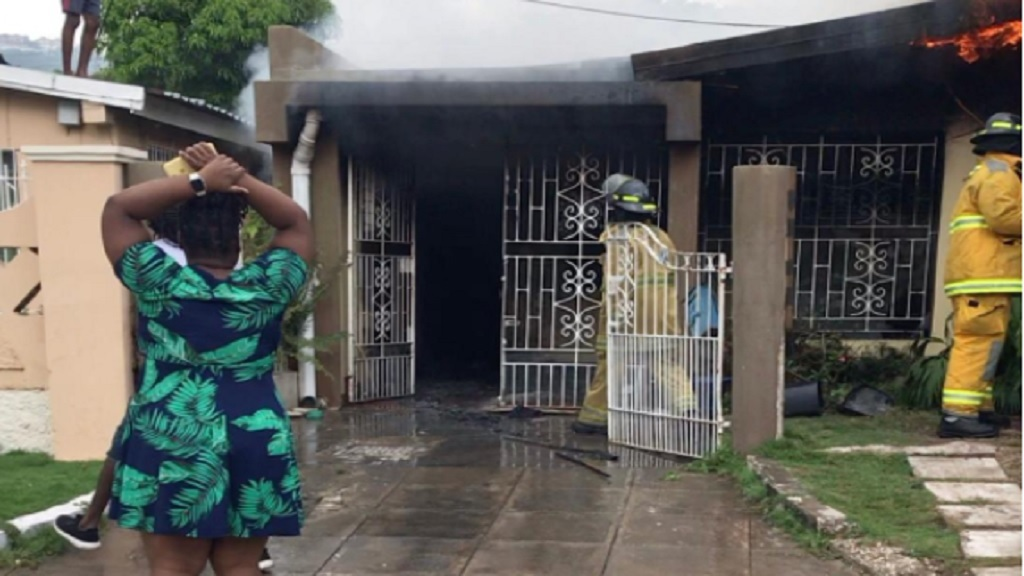 A woman, believed to be an occupant of the house in focus, in desolation amid cooling down operation after a fire in Pembroke Hall, St Andrew on Wednesday afternoon.